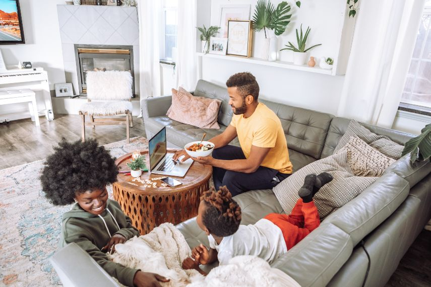 Family sitting on couch with laptop